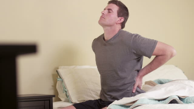 Man sitting on bed with back pain video
