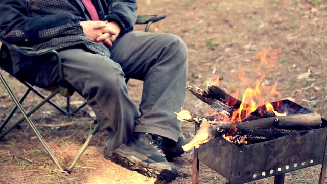 Man sitting on camp chair near bonfire. Outdoor recreation. Campfire in forest video