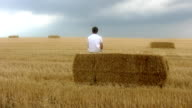HD SLOW MOTION: Man Sitting On Hay Bale video