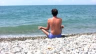 man sitting on rocky beach in pose of lotus video