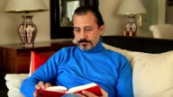 Man sitting on sofa and reading book video