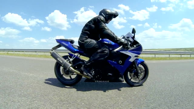 Man sitting on the motorcycle and moving on the road video