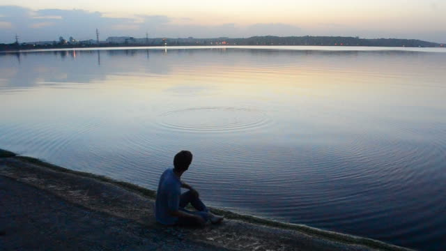 Man skips stones on water in the evening video