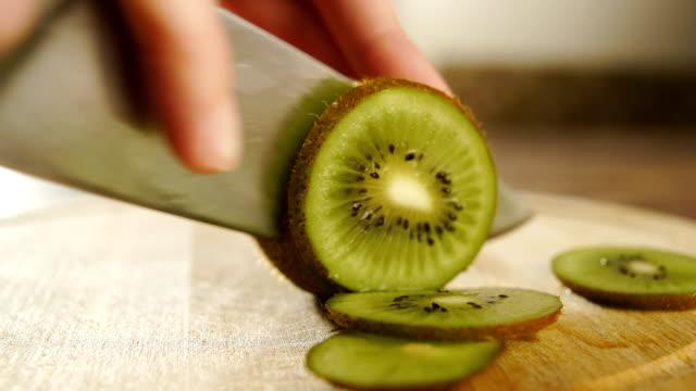 Man slicing kiwi fruit video