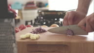 Man slicing red onion on cutting board video