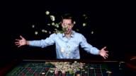 Man smiles hugely as tosses winnings in the air. Black video