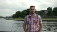 Man smiling to camera by the river. video