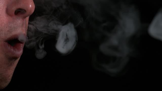 Man smoking a Cigarette against Black Background, Slow Motion 4K video