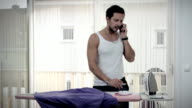 Man smoking and talking on the phone while ironing video