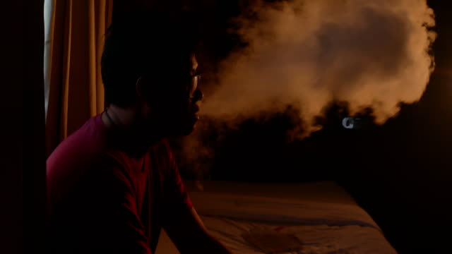 man smoking electric e cigarette vapor in dark room video