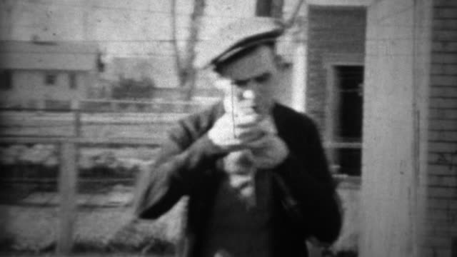 1934: Man smoking pipe outside house original backwards play art. video