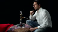 Man smoking water pipe, isolated on black background video