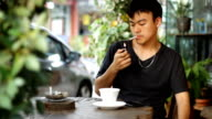 man smoking while using smart phone and drink coffee video