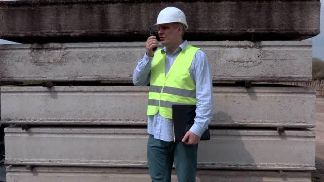 Man speaking on walky talky near construction blocks video