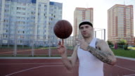Man spinning a basketball on his finger on the at district sports ground background of residential buildings. video