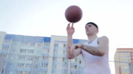 Man spinning a basketball on his finger on the background of residential buildings. video