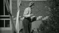 1935: Man spraying pesticide herbicide chemicals on rose bushes. video