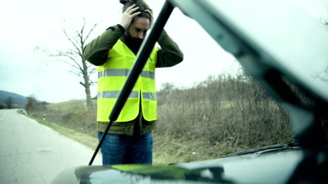 Man standing next to broken car video