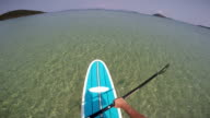 POV man standing on a paddle board in tropical waters video