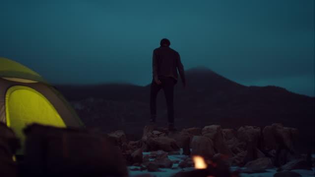 Man standing on rocks cheering video