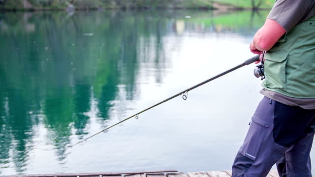 Man standing on the shore an fishing in the local lake in the middle of a countryside, footage is in slow motion. video