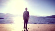 Man standing on the shore of lake at sunrise video