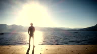 Man standing on the shore of lake at sunset video
