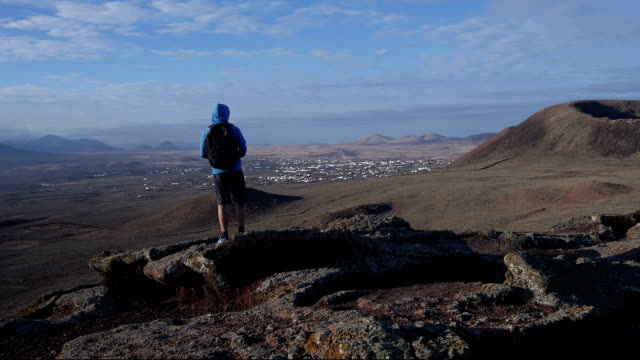 AERIAL: Man standing on top of volcano admiring the view video