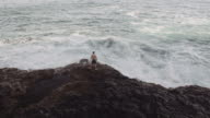 Man standing shirtless next to the ocean video