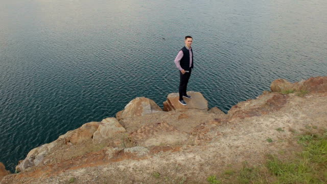 Man stands on the edge of the cliff near the lake. video