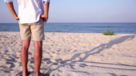 Man stands on the sand beach at sunset enjoying calm sea video