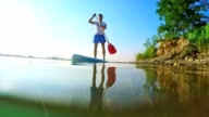 SLO MO Man stand-up paddleboarding on the lake video
