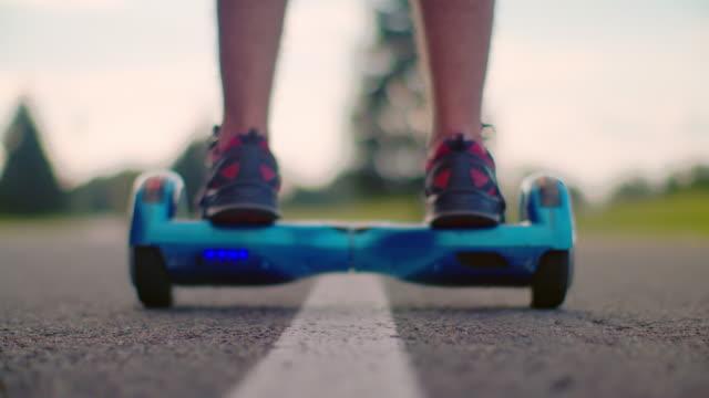 Man start moving on gyro scooter at asphalt road. Man on self balance hoverboard video