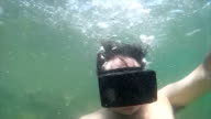 Man starts at ocean surface, then submerges with VR goggles blowing numerous bubbles video