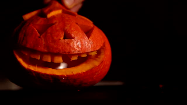 Man starts fire in Halloween Jack-o'-lantern .Horror smile lights in the dark video