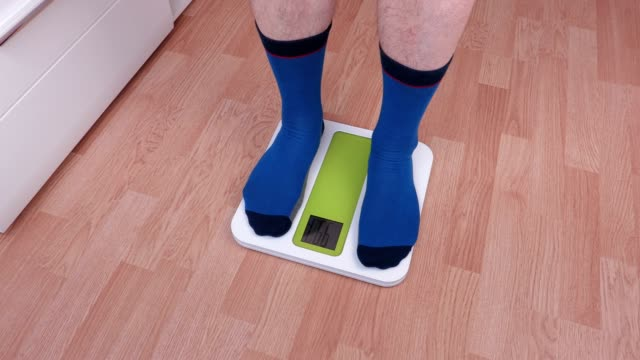 Man step up on electronic scale and try to fix weight video