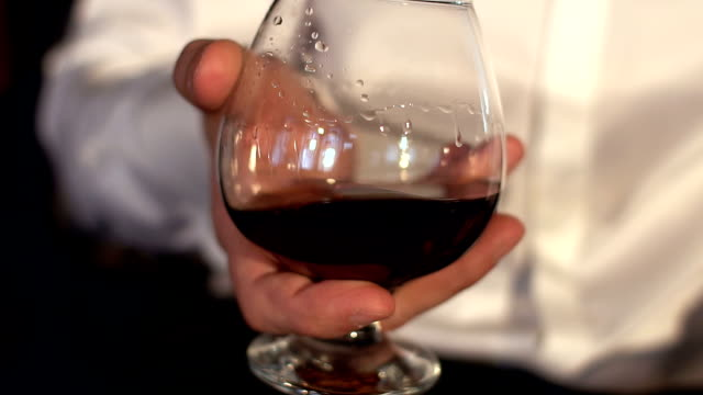 Man stir slowly cognac in the glass, slow motion.Glass of whiskey in male hands. video