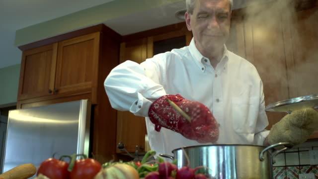 Man stirring a pot full of hot food video