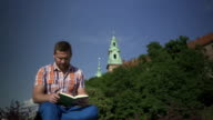 Man stops reading book and looking round. video