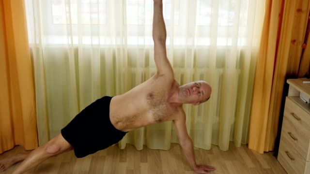 Man stretching core muscles by tilting and twisting his hands. Indoors living room training yoga. video