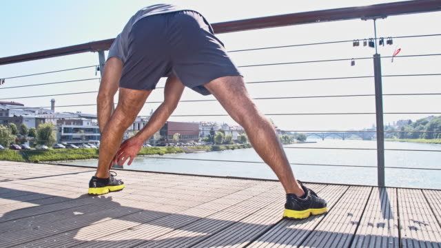 Man stretching on a bridge video
