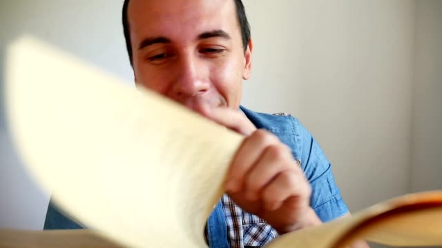 man surprised joyful thinks reading turns the page video a book sitting in the room video