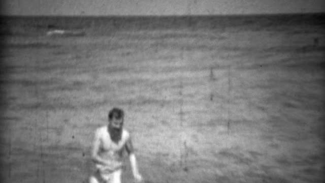 1936: Man swimming in underwear pulling it up along ocean beach. video