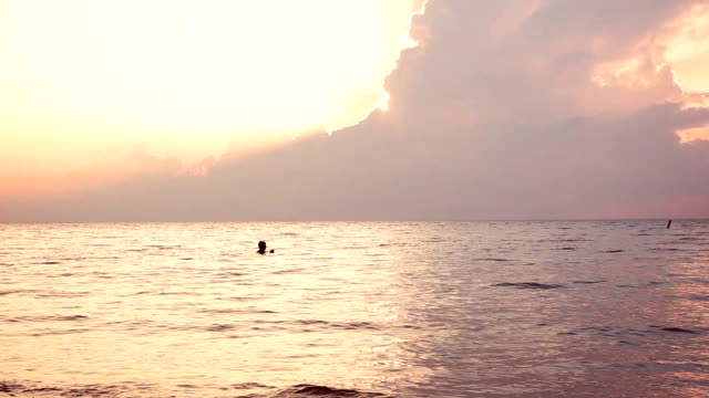 Man swims in the ocean near sunset in the summer video