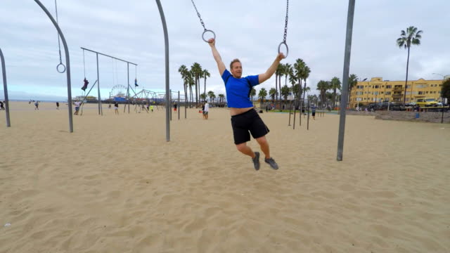 Man Swinging on Gym Rings at Venice Beach Los Angeles video