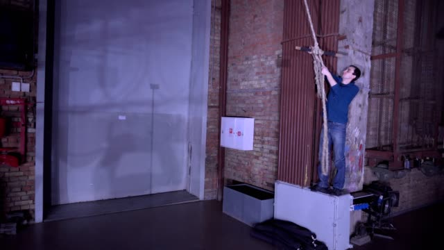 Man swings on a rope swing indoor video