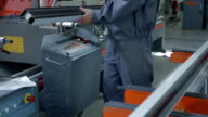 Man takes metal frame and puts it into cutting machine video