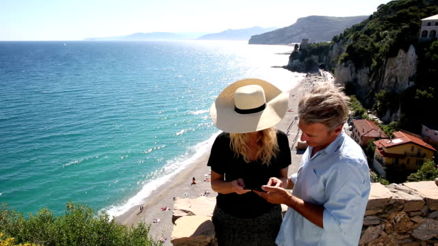 Man takes pic of woman on stone wall above beach video