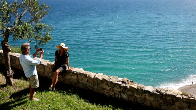 Man takes pic of woman on stone wall above sea video