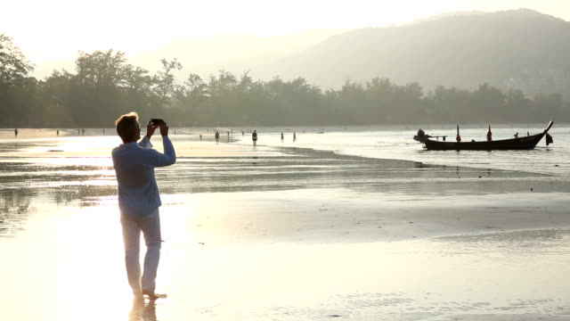 Man takes picture with smart phone, on beach at sunrise video